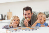 Smiling father and his sons eating cookies — Stock Photo