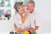 Old man tasting vegetable held by wife — Stock Photo