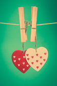 Two heart ornaments hanging from pegs on a line — Stock Photo