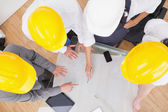 Team looking at a construction plan with hard hats — Stock Photo