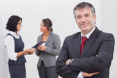 Businessman smiling and two businesswomen speaking — Stock Photo