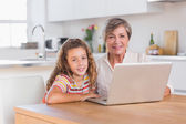 Child and granny looking at the camera with laptop — Stock Photo