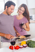 Couple preparing food and drinking — Stockfoto
