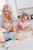 Mother making a face while her children take care of the dough — Foto Stock