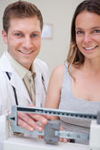 Doctor and patient setting up scale — Stock Photo