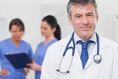 Doctor with stethoscope smiling and his team behind him — Stock Photo