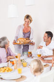 Mother bringing turkey to dinner table — Stock Photo