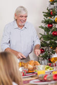 Grandfather carving christmas turkey — Stock Photo