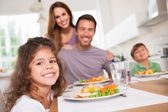 Famille, souriant à la caméra à table — Photo