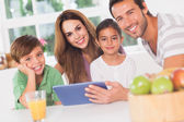 Happy family using a tablet pc — Stock Photo