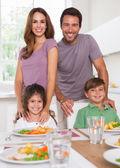 Twee kinderen en hun ouders glimlachen op de camera op diner t — Stockfoto