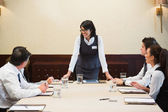 Happy businesswoman standing at head of table — Stock Photo