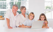Children and grandparents looking at the camera together with la — Stock Photo