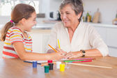 Child with her granny drawing and laughing — Stock Photo