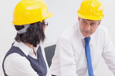 Two architects speaking with yellow helmet — Stock Photo
