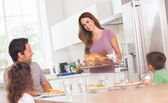 Mother bringing roast turkey to table — Stock Photo