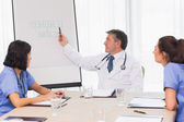 Doctor pointing to board during meeting — Stock Photo