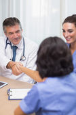 Smiling doctor shaking nurses hand — Stock Photo