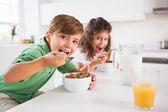 Duas crianças olhando para a câmera enquanto a comer cereais — Foto Stock