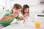 Two children looking at camera while eating cereal — Stock Photo