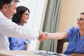 Nurse and doctor shaking hands — Stock Photo