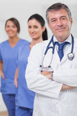 Doctor with arms crossed and his team of nurses — Stock Photo