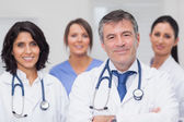 Two doctors and two nurses smiling — Stock Photo