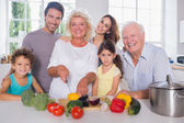 Multi-generation family cutting vegetables together — Stock Photo