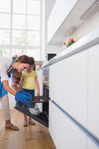 Mother taking cookies out of the oven — Stock Photo