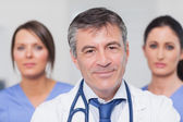 Smiling doctor with two nurses — Stock Photo