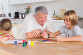 Grandfather and her grandchildren drawing — Stock Photo