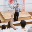 Teacher in front of futuristic interface pointing a student — Stock Photo
