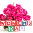 Bunch of pink roses next to wooden blocks spelling womens day — Stock Photo #24146297
