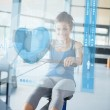 Young girl doing rowing machine with futuristic interface — Stock Photo