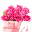 Bouquet of beautiful pink roses next to a pink gift with a happy - Stock Photo