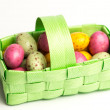 Speckled colourful easter eggs in a green basket — Stock Photo