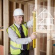 Stock Photo: Architect using spirit level and looking at white hologram inter