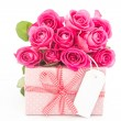Bouquet of beautiful pink roses next to a pink gift with an empt - Stock Photo