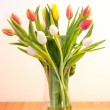 Vase of tulips on wooden table — Stock Photo
