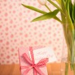 Vase of tulips on wooden table with pink wrapped gift and mother - Stock Photo