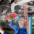 Stock Photo: Mechanic under car consulting interface