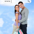 Happy couple with their shopping bags under address bar — Stock Photo