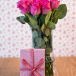 Stock Photo: Bunch of pink roses in vase with pink gift leaning against it