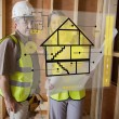 Architect and foreman standing behind house plan interface — Stock Photo