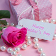 Stock Photo: Pink rose with gift and string of pearls for mothers day