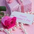 Pink rose with gift and string of pearls for mothers day — Stock Photo