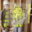 Architect and foreman checking the plans on interface — Stock Photo