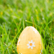 Orange easter egg sitting in the grass — Stockfoto