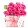 Bouquet of pink roses next to a pink gift with a happy mothers d - Stock Photo