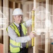 Architect using spirit level while looking at white hologram int - Stock Photo